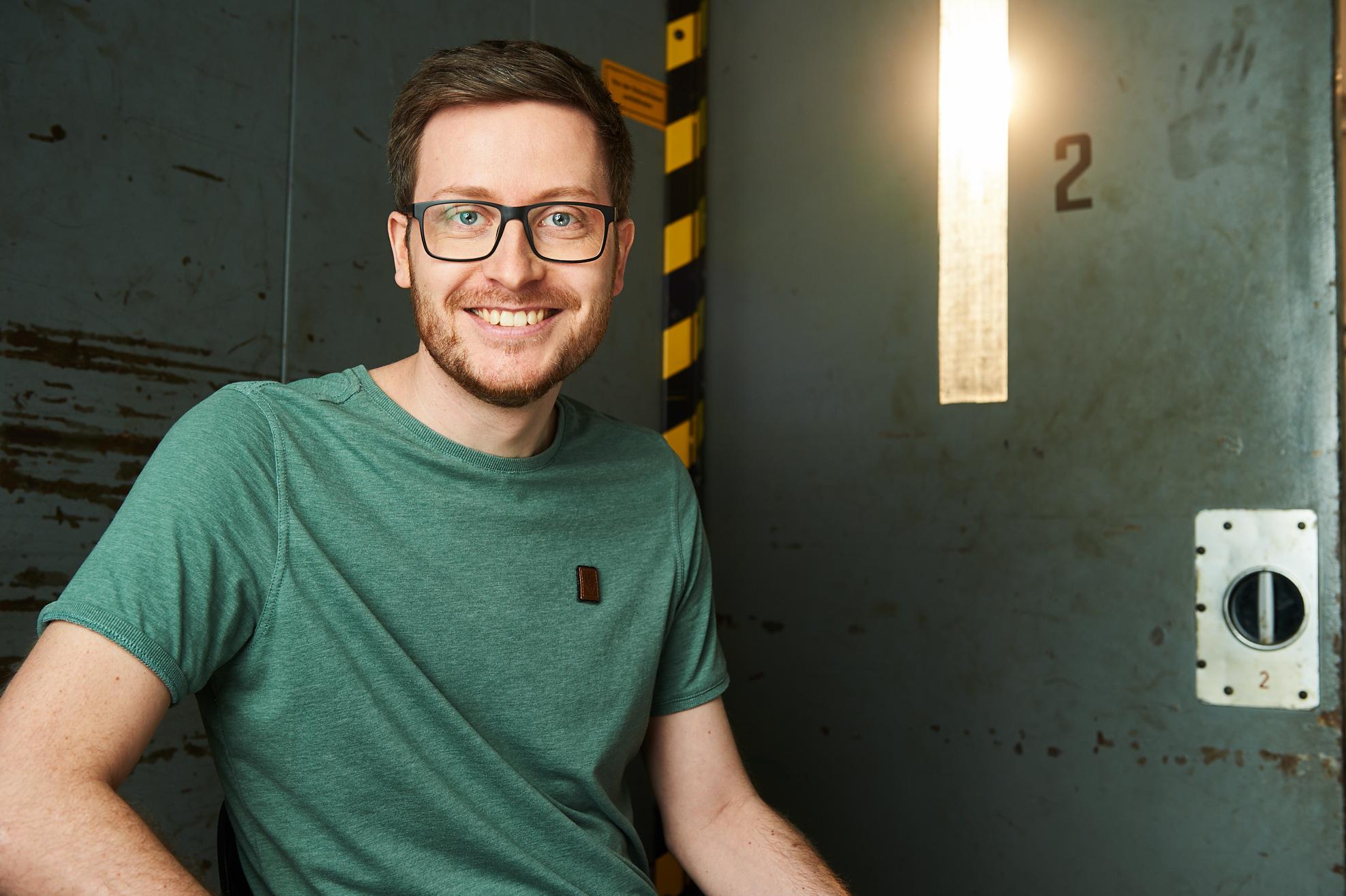 Christian Troitzsch lächelnd sitzend vor einer grünen industriellen Metalltür