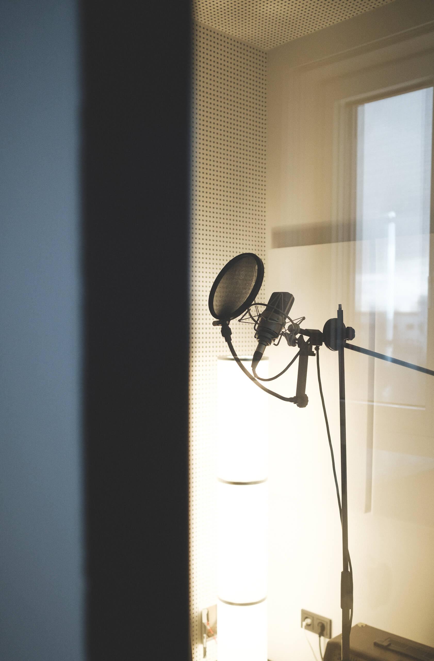 Ein Mikrofon mit Poppschutz in einer Gesangskabine